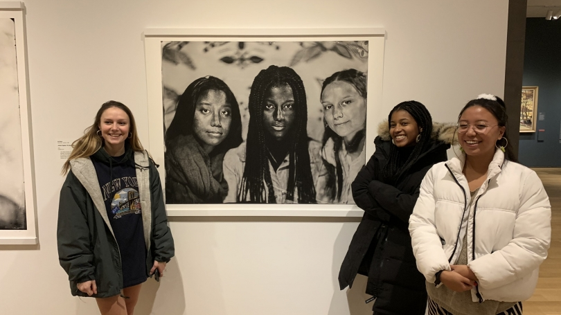 In the gallery, three young women smile alongside a large black and white photograph. That photograph depicts those three women.