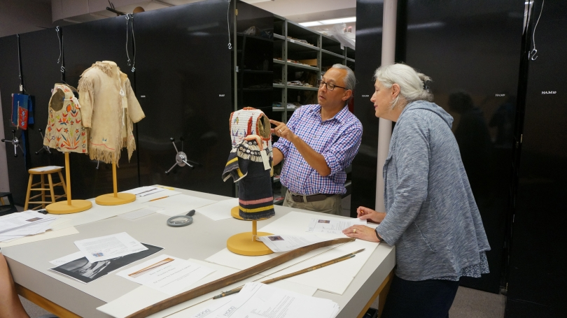 Joe Horse Capture, visiting curator and consultant, examines objects from the collection with Hood Collections Documentation Manager and Cataloguer Deborah Haynes, in July 2015. Photo by Alison Palizzolo.