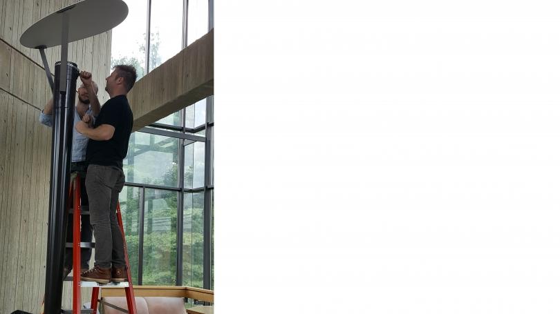 Hood Museum of Art Preparator Matt Zayatz and Dartmouth student Josh Davis prepare to install a fourth floor speaker as part of Transmission.