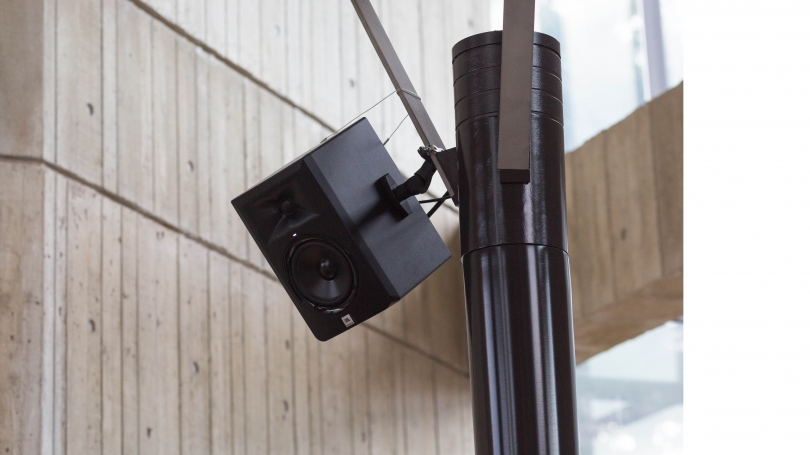 Detail of the one of the fourth-floor speakers secured on a light pole. The speaker is tilted down to direct the sound.