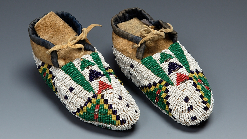 Child's moccasins made by a Lakota artist, about 1900, Native-tanned hide, glass beads, metal beads, ribbon, thread