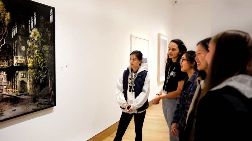 Museum Club members Ivy Yan '22 and Sydney Sims '21 speak with students about Lori Nix's Library (2007) during the fall 2019 Hood After 5 student party. Photo by Seth Weprin '23.