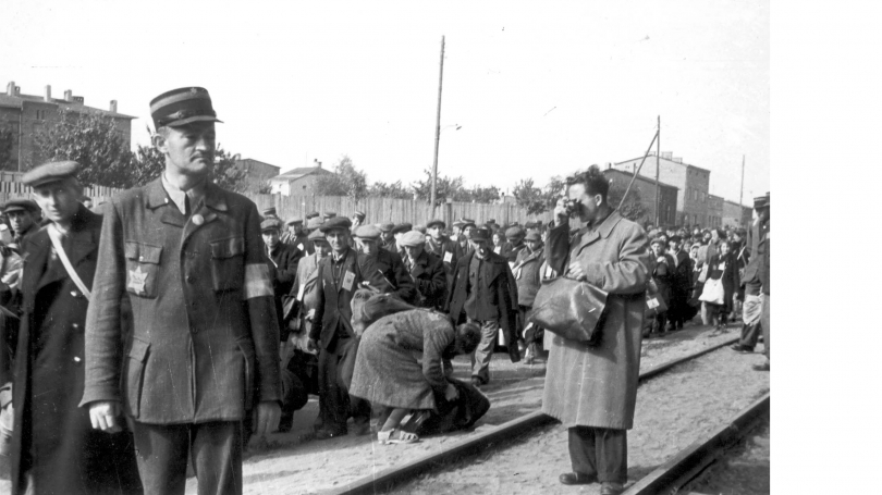 Łódź ghetto photographer Mendel Grossman clandestinely photographing the deportation of Jews. The photo was taken by Grossman's assistant, Aryeh Ben-Menachem. Courtesy of Yad Vashem Archives.