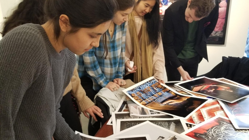 A group of students looks at photographs on a table.