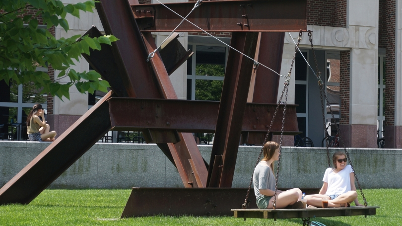 Dartmouth students relax on Mark di Suvero's X-Delta (1970) while enjoying the spring weather