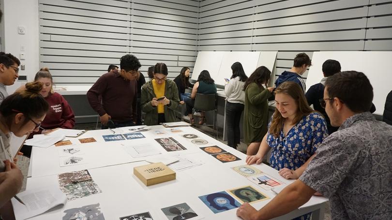 Students look at prints in Borderlands Art and Theory taught by Tatiana Reinoza. Photo by Randall Kuhlman.