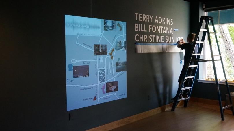Hood Museum of Art Preparator Matt Zayatz installs artists' names at Hood Downtown.