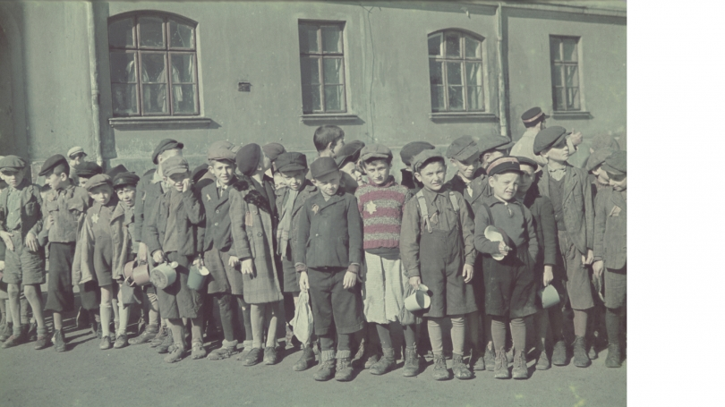 Walter Genewein, Ghetto Schoolchildren Holding Small Pails and Cups Wait in Line outside the Ghetto Soup Kitchen, 1941. United States Holocaust Memorial Museum: Courtesy of Robert Abrams; 74514A.