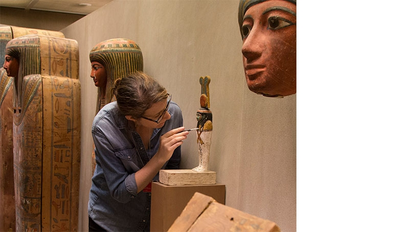 Conservator Anna Serotta '03 examines an object from the Egyptian Art collection at The Metropolitan Museum of Art