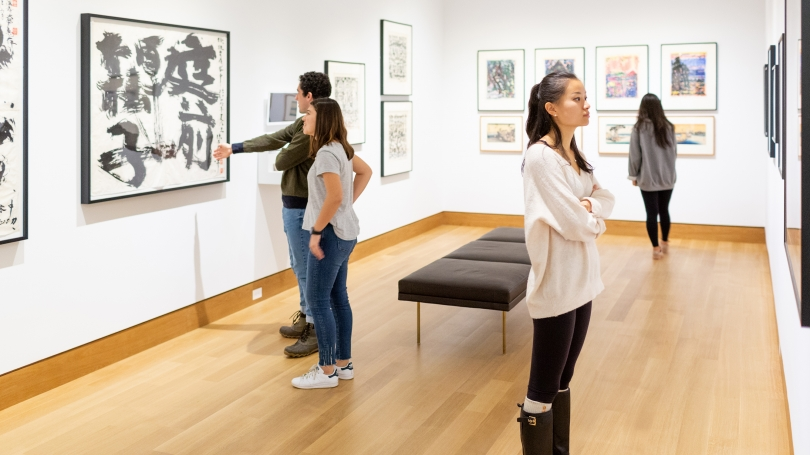 Dartmouth students explore an installation of Japanese prints in the new Class of 1967 Gallery at the foot of the stairs in the renovated museum. Photo by Rob Strong.