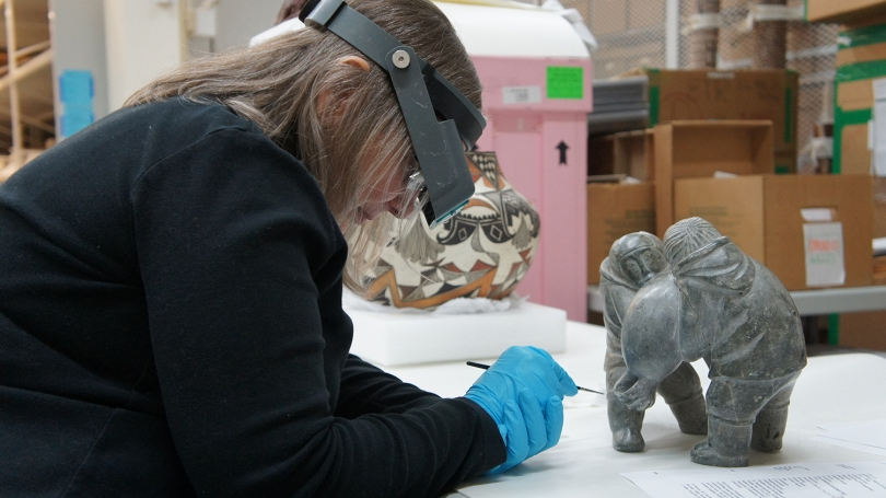Hélène Gillette-Woodard, conservator of objects, Williamstown Art Center, inpaints a scratch on a Canadian Inuit soapstone sculpture, Two Hunters Carrying a Seal, having previously consolidated the area with Paraloid B-72