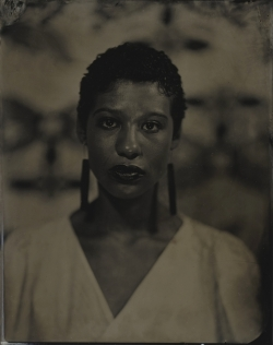 A tintype portrait of a woman of color. She faces the viewer and is photographed from the chest up.